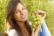 Glückliche Frau hält grüne Trauben hoch