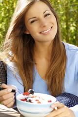 Glückliche Frau ißt Müsli zum Frühstück