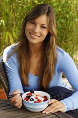 Glückliche Frau ißt Müsli auf der Terrasse