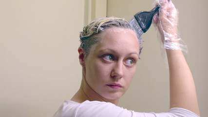 Blonde woman doing her hair dye