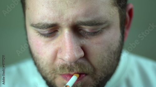 Bearded man lighting and smoking a cigarette