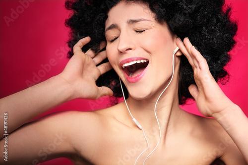 Woman with afro hair enjoying music