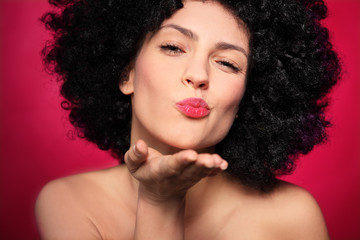 Woman with afro blowing a kiss