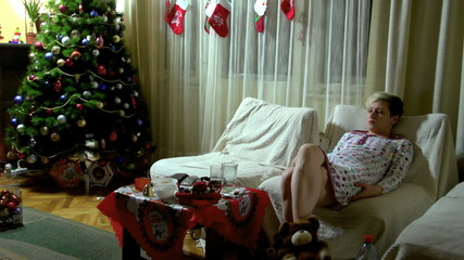 Woman sitting on a sofa at Christmas evening