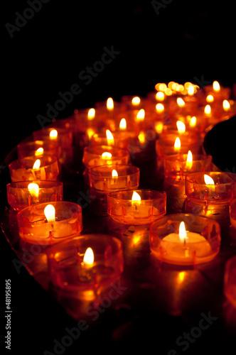 Viele Lichter vor schwarzem Hintergrund in einer Kirche