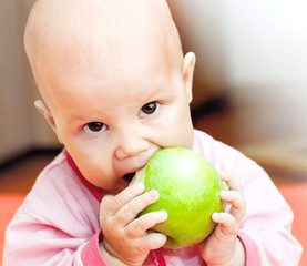Little baby eats green apple and looks in the camera