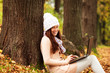 Beautiful student girl with laptop in autumn park.