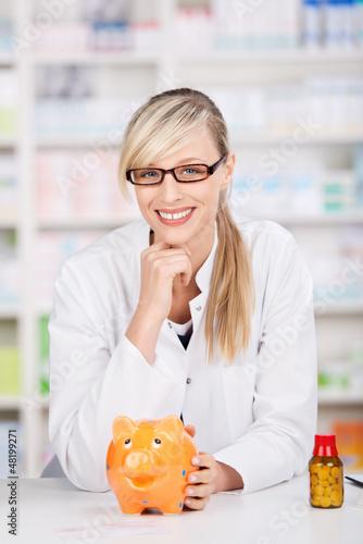 lächelnde apothekerin mit sparschwein