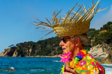 senior man with cocktail drink at the beach