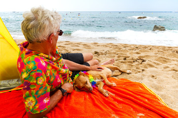 man laying with dog at the beach