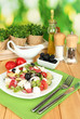 Fresh greek salad on plate on wooden table on natural