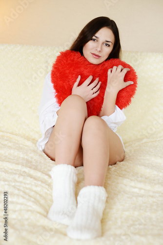 brunette woman with heart pillow