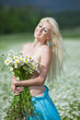 Attractive blonde in chamomile field