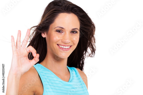 pretty young woman giving ok hand sign over white background