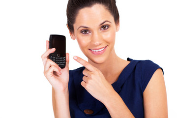 cute young woman pointing at smart phone isolated