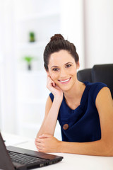 cheerful pretty woman sitting in front of laptop