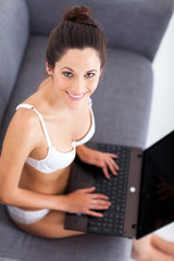 pretty young woman in underwear using laptop on sofa