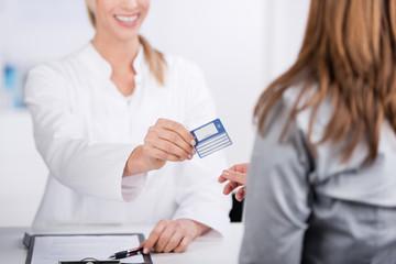 patientin und arzthelferin mit versicherungskarte