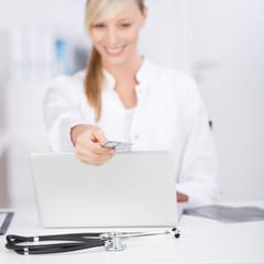 lächelnde arzthelferin überreicht versicherungskarte