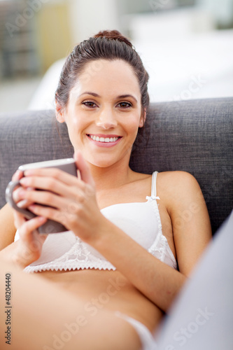 attractive young woman in underwear relaxing at home with coffee