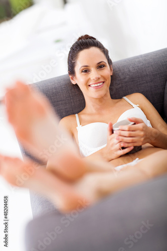 attractive young woman in underwear relaxing on sofa
