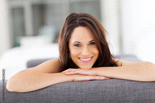 cheerful young woman lying on sofa laughing