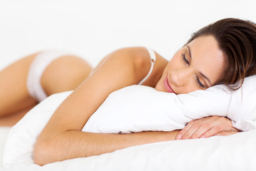 peaceful young woman sleeping on bed