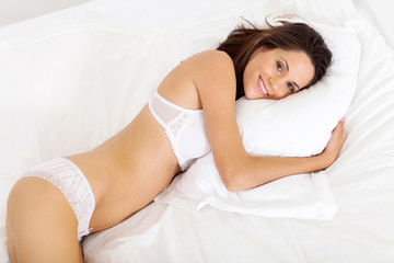 cute young woman lying on bed
