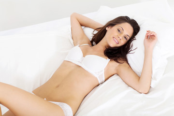 pretty woman in lingerie lying on bed