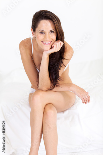 happy young woman in underwear sitting on bed