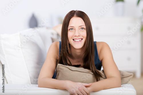 lächelnde junge frau liegt auf dem sofa