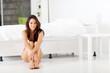 beautiful young woman sitting on bedroom floor