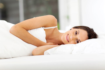 beautiful young woman smiling and sleeping on bed