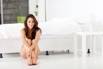 beautiful young woman sitting on bedroom floor