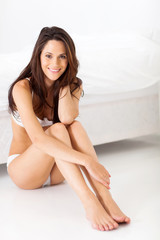 sweet young woman sitting on bedroom floor