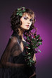 Portrait of a young brunette in makeup and beautiful flowers