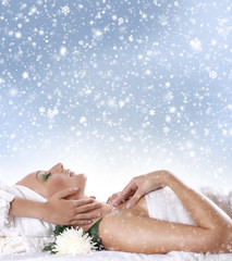 A young woman laying on a spa procedure on a snowy background