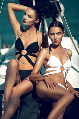 two beutiful girls are posing on the yacht