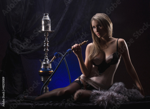 A young and sexy blond woman smoking a hookah