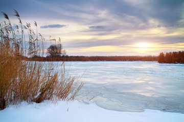 Winter landscape with sun and frozen river.