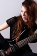 Beautiful girl in black plays black bass guitar