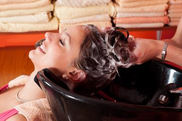 Beautiful young girl enjoying hair washing in hairdressing salon