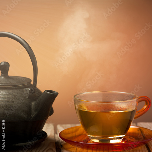 Teapot and a cup of tea on an old wooden table - hot steam smoki