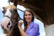 Junge Frau im Stall mit Pferd bei Sonnenschein