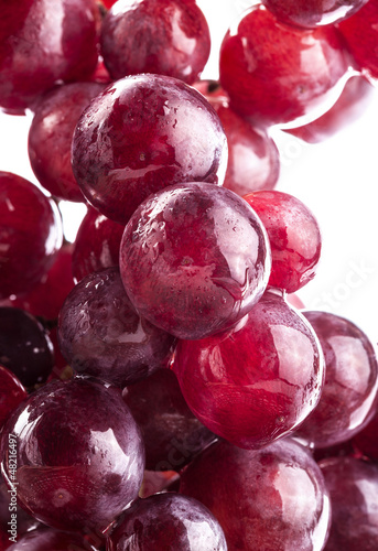 Ripe grapes with water drops, on white background