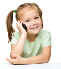 Cute little girl is talking on a cell phone