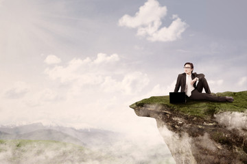 Businessman sit on top of mountain