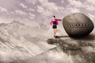 Businesswoman and rock of success outdoor