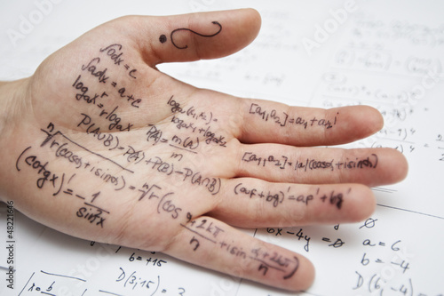 Hand of student with cheat sheet for math exam