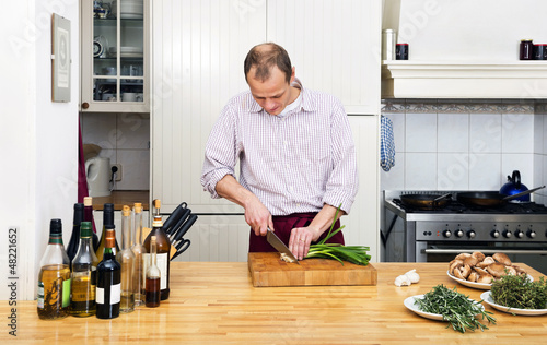 Man Cutting Spring Onions In Kitchen
